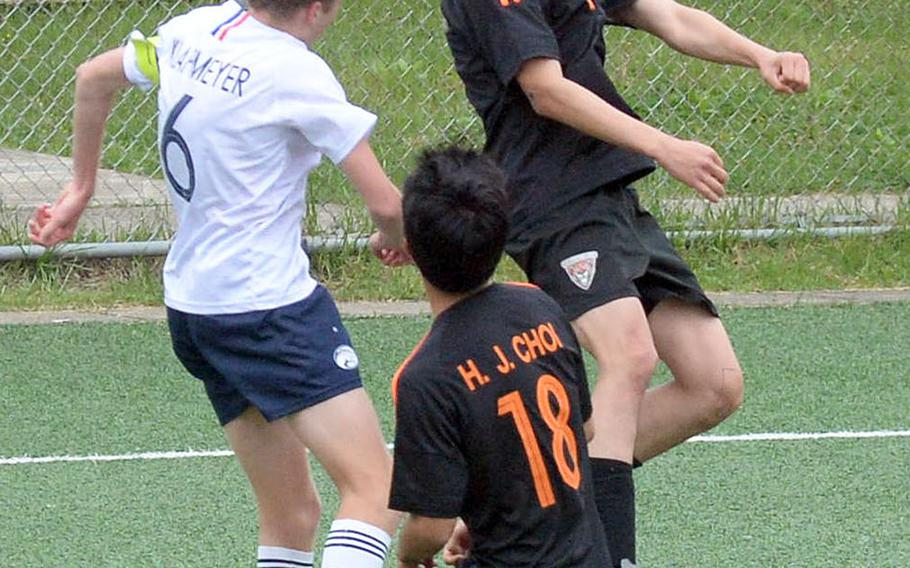 Seoul International's Archie Lee heads the ball against Osan's Ryan Klapmeyer during Friday's Korea boys soccer Plate Tournament at Osan Air Base. The host Cougars won 3-0.