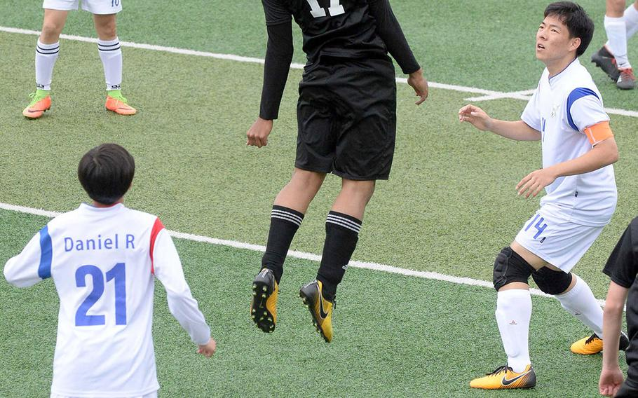 Daegu's Sam Murphy heads the ball, surrounded by International Christian-Pyongtaek players, during Friday's Korea boys soccer Plate Tournament match at Osan Air Base. The Conquerors won 3-1.