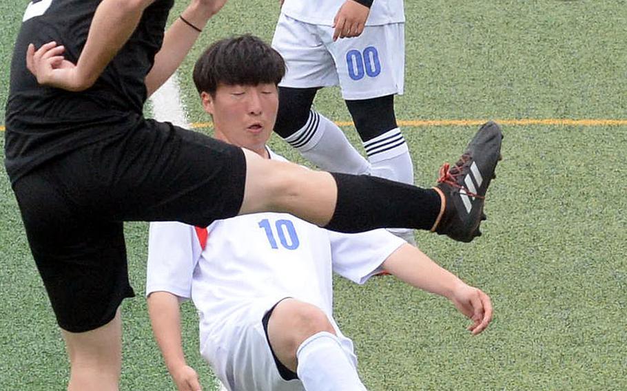 Daegu's MIciah Ruff leaps up to kick the ball against International Christian-Pyongtaek's Don Lee during Friday's Korea boys soccer Plate Tournament match at Osan Air Base. The Conquerors won 3-1.