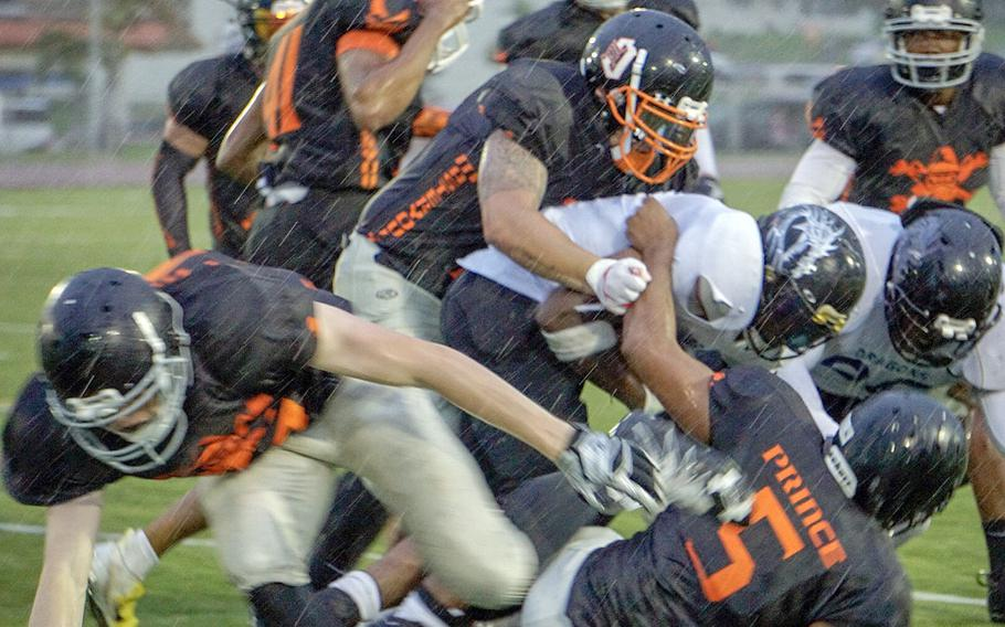 Hansen's Caine Collins leads a pack of Hansen Outlaws defenders, bringing down an Okinawa Dragons ballcarrier in the driving rain of the second quarter of the Torii Bowl.