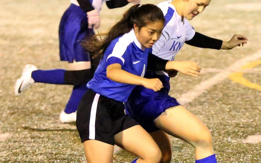 Christian Academy Japan's Maika Edberg and Yokota's Emma Oshiro chase the ball with Knights teammate Kaitlyn Corbett in trail above during Tuesday's Japan girls soccer match, won by the Panthers 2-0.