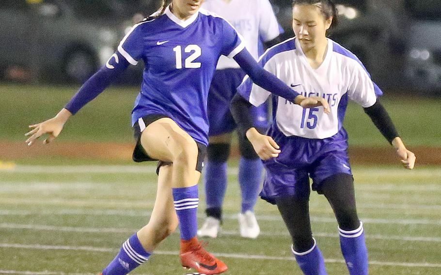 Yokota's Chloe Dozier works the ball against Christian Academy Japan's Keziah Sou during Tuesday's Japan girls soccer match, won by the Panthers 2-0.
