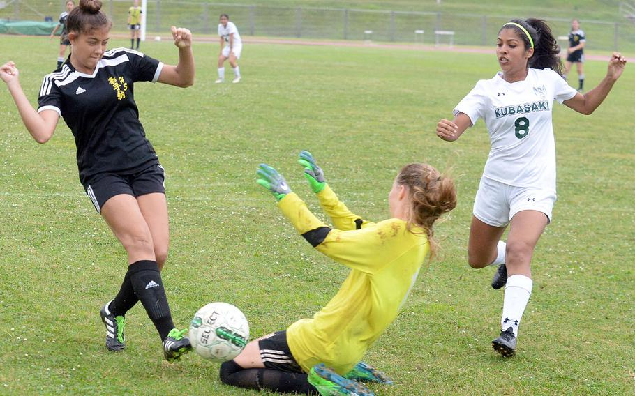 Kadena's Alexa Smith and Kubasaki goalkeeper Abbigail Irwin nearly collide after Smith sends a shot wide of the net, as Dragons' Angelica Figueroa looks on during Friday's Okinawa girls soccer match. The Panthers won 7-2 to sweep the season series.