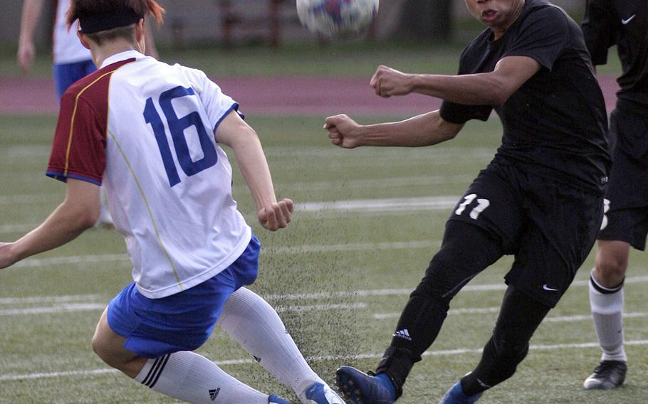 Zama's Justyn Seraphin boots the ball against an Aoba International opponent during Friday's Japan boys soccer match, won by the Trojans 4-1.