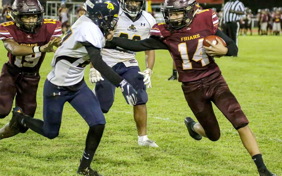 Father Duenas' William Ludwig tries to turn the corner and stiff-arms Guam High defender Gino Rameriz.