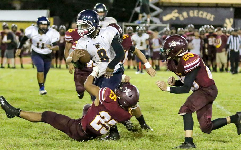 Guam High running back Jayson Jackson tries to elude the defense of Father Duenas' Gene Arriola and Kekoa Gamboa.