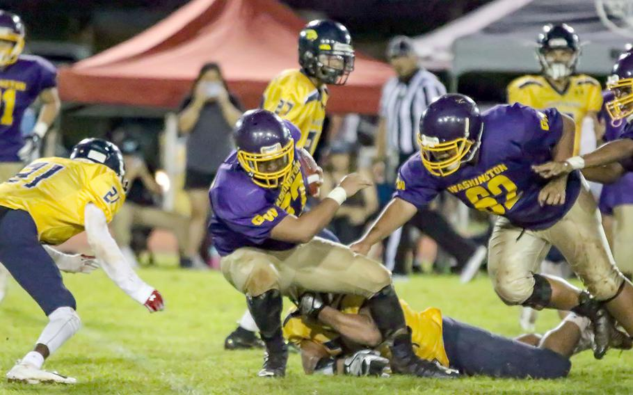 George Washington's Eian Naputi tries to squirt free from a Guam High defender.
