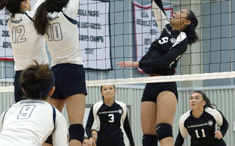 Humphreys' Natalie Goode tries to hit through the double block of Yongsan's Megan Paek and Sumi Fertig during Wednesday's Korea girls volleyball match, won by the Guardians 3-1.