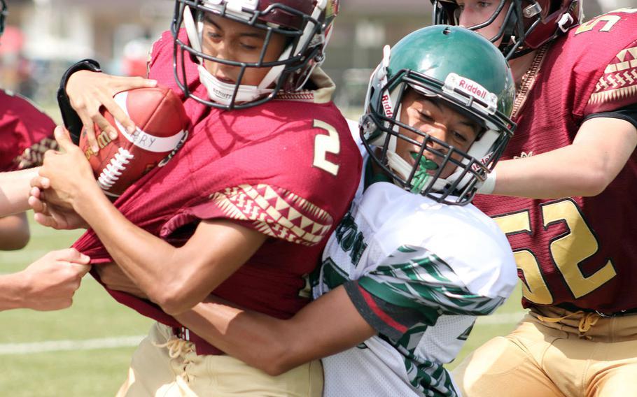 Matthew C. Perry quarterback Joel Pacleb gets wrapped up by Daegu's Jayson McCode.