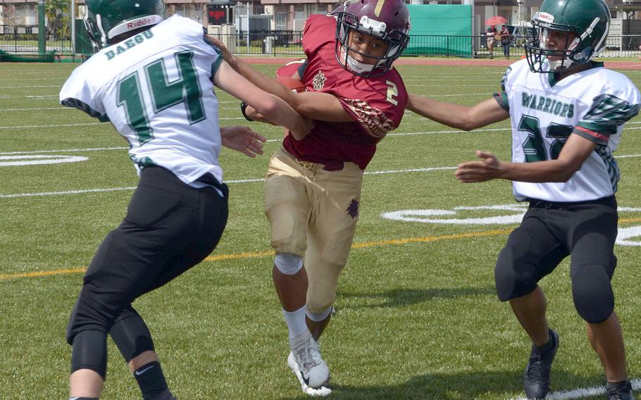 Matthew C. Perry quarterback Joel Pacleb tries to drive past Daegu's Andrew Reeves and Jayson McCode.