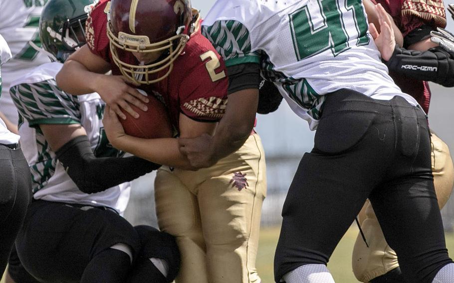 Matthew C. Perry quarterback Joel Pacleb tries to knife his way through the Daegu defense.