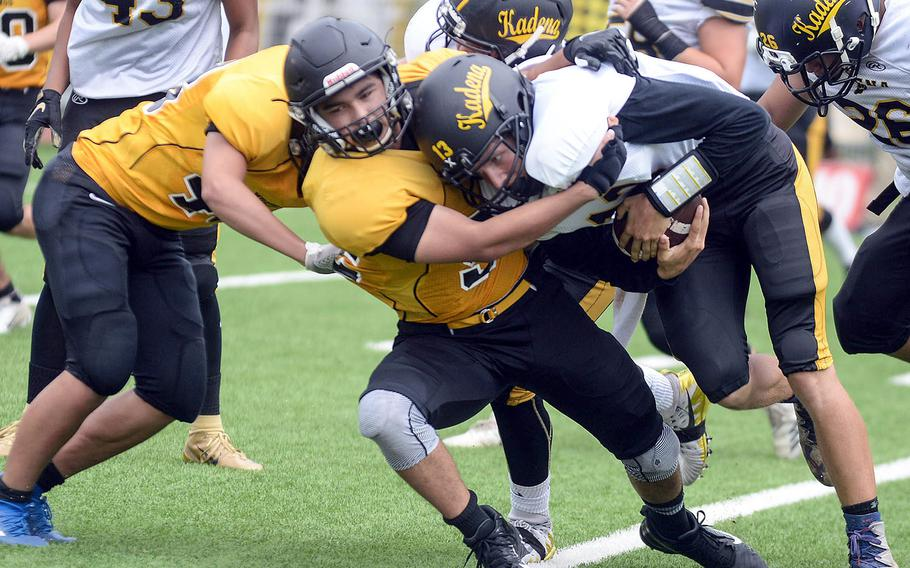 Kadena quarterback Jack Carey gets wrapped up by several American School In Japan defenders.