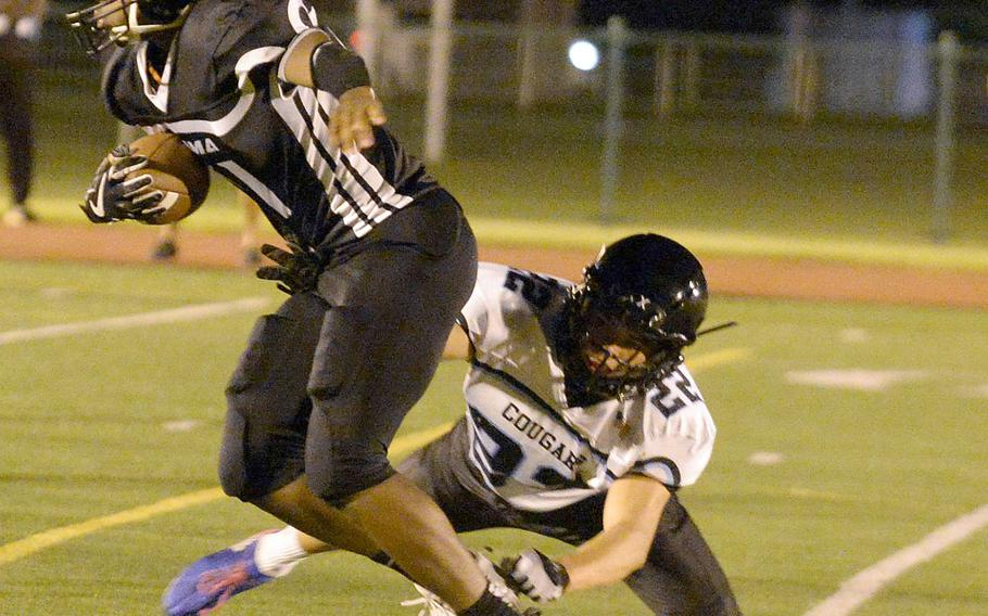 Zama's Brenden Jackson sheds a tackle by Osan's Marcus Inthavixay en route to a 20-yard catch-and-run for a touchdown.
