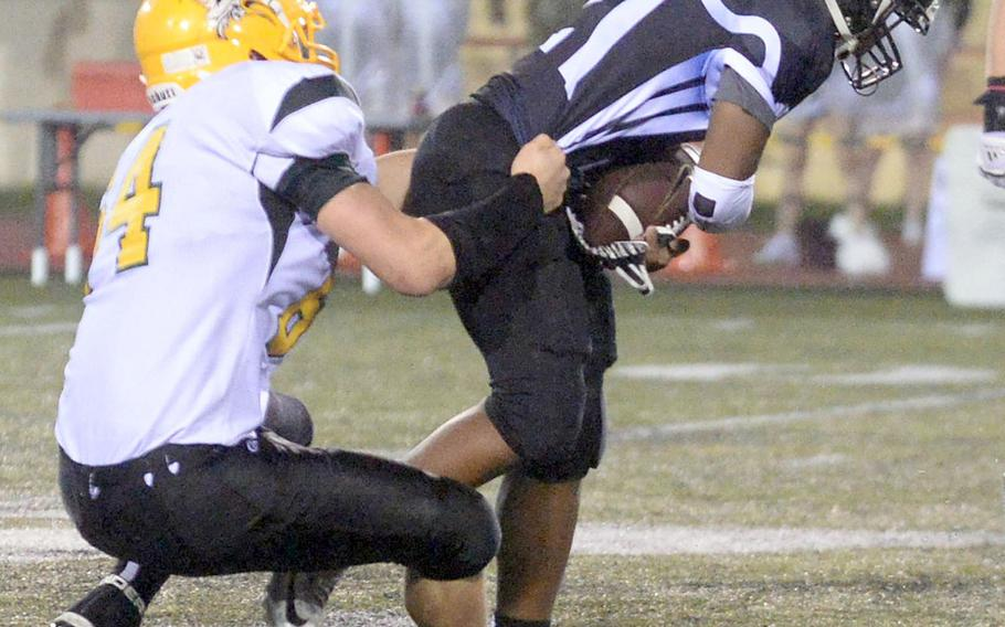 Zama running back Brenden Jackson gets wrapped up by Robert D. Edgren defender Chase Quigley.