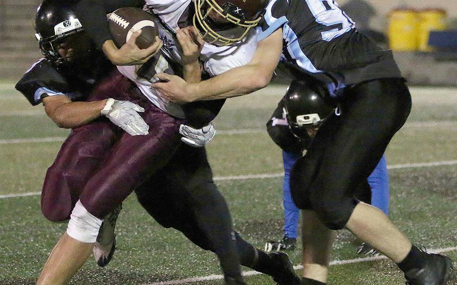 Matthew C. Perry running back Matthew Torrecillas gets hemmed in by Osan's Zathian Soto and Jacob White.