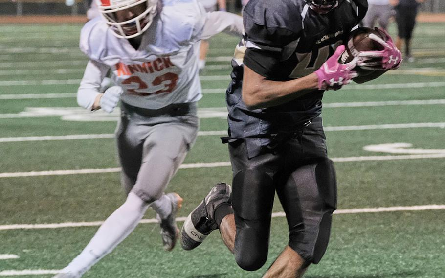 Humphreys' Junior Gregory hugs the sideline with a 60-yard touchdown catch in front of Nile C. Kinnick's Ryo Nishiyama.