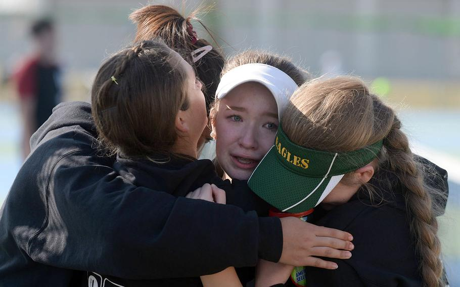 An emotional Jenna Mahoney gets a group hug from Robert D. Edgren teammates after winning the DODEA-Japan tournament girls singles A title for the second straight year.