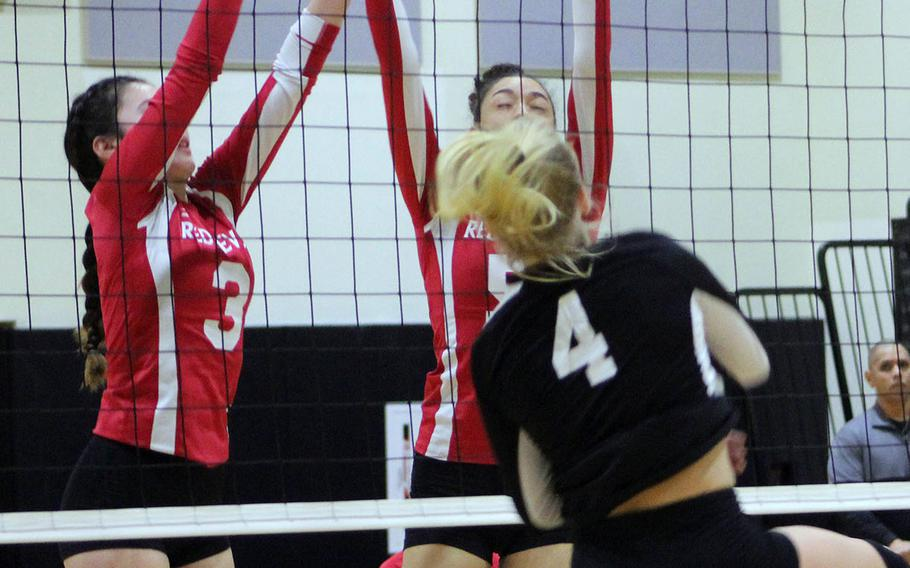 Nile C. Kinnick's Alyssa Lynch and Ernestina Roberts go up to block Humphreys' Zoe Weidley during Thrusday's Far East Division I volleyball tournament pool match. The Blackhawks won in two sets.