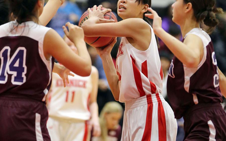 Kinnick's Amyka Jones looks to pass against Seisen defenders Lisa Purcell and Momone Ishibashi during Thursday's Kanto Plain girls basketball game. The Red Devils won 44-35 in overtime.