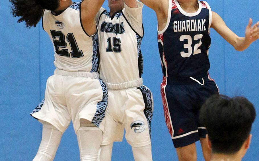 Osan's Ryan Klapmeyer and Israel Rouse battle Yongsan's Nathan Hong for a rebound during Wednesday's Korea Blue boys basketball game. The Guardians won 61-16.