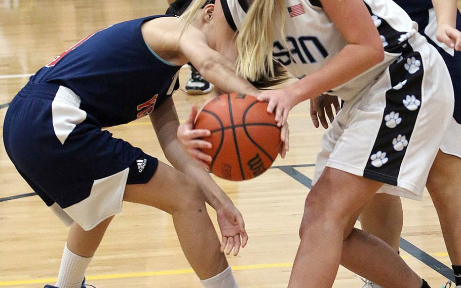 Osan's Katelyn Edmunds battles Yongsan's Sophia Lee for the ball during Wednesday's Korea Blue girls basketball game. The Guardians won 50-33.