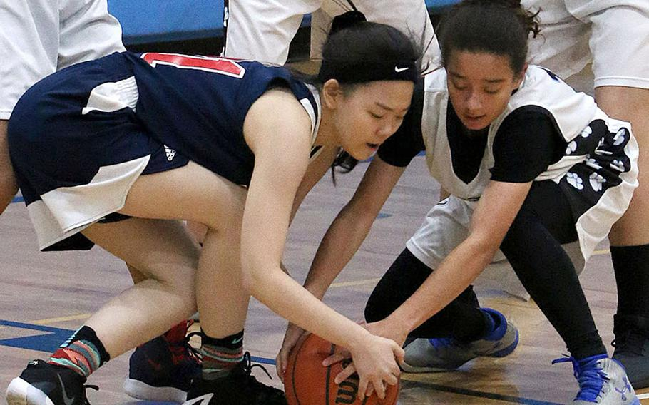 Gimme that ball! Yongsan's Isabelle Park and Osan's Dawn Kerlin battle for the ball during Wednesday's Korea Blue basketball game. The Guardians won 50-33.
