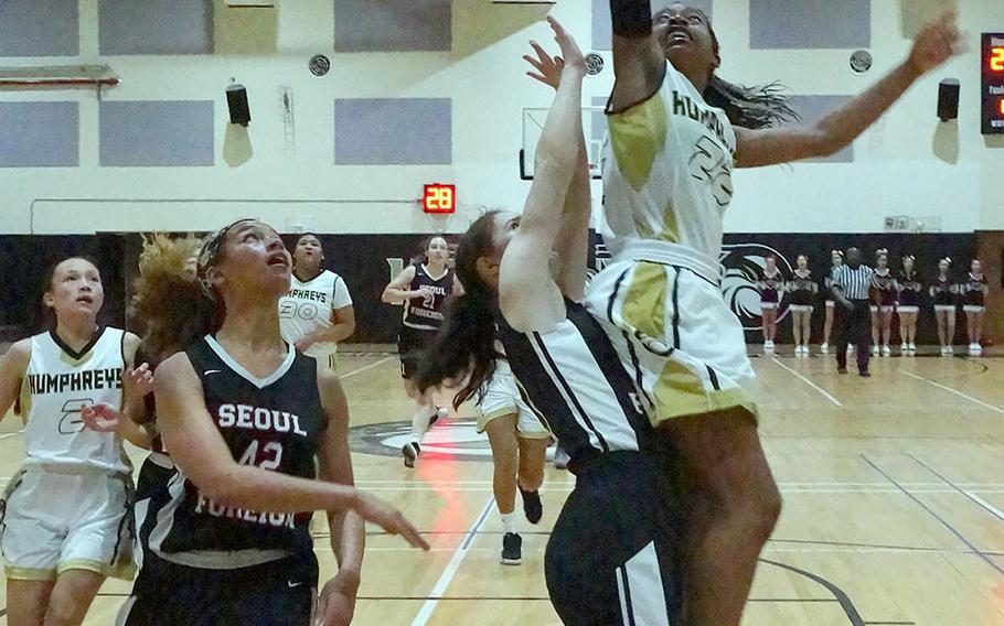 Humphreys' Jaylynn Knight goes up for a shot against Stella Nas and Mya Rolison of Seoul Foreign. The Blackhawks won 53-28. Knight and Rolison played together last season at Seoul American, now closed.