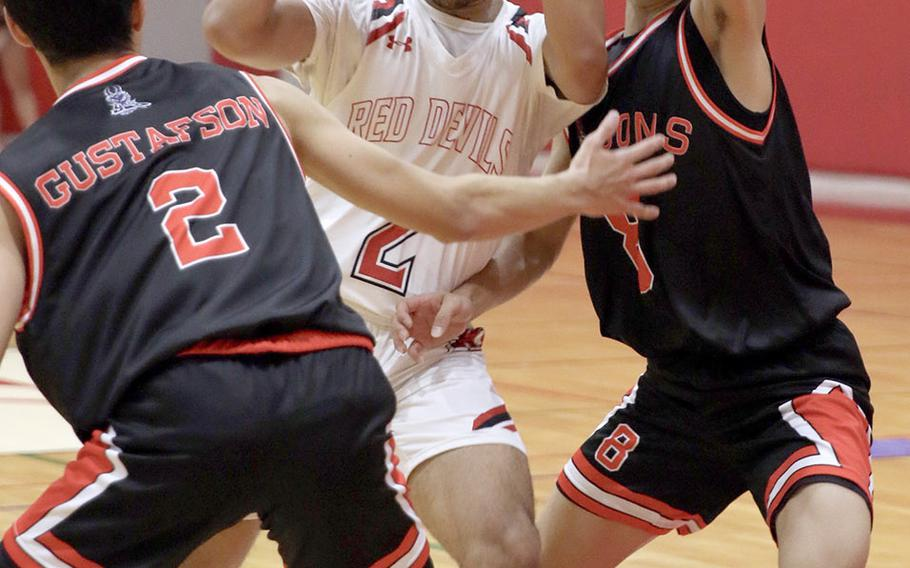 Nile C. Kinnck's James Mincey drives between two Yokohama defenders during Friday's Kanto Plain boys basketball game. The Red Devils won 72-49.