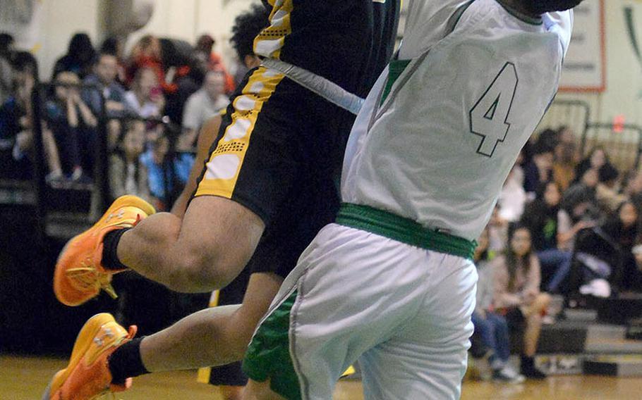 Kadena's Casey Cox shoots against Kubasaki's Mason Taylor during Friday's Okinawa boys basketball game. The Panthers won 72-37.