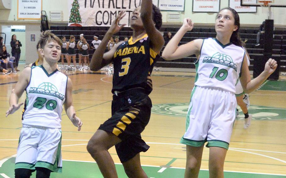 Kadena's Christee Dervil drives between Kubasaki's Ari Gieseck and Sophie Grubbs during Friday's Okinawa girls basketball game. The Panthers won 45-15.
