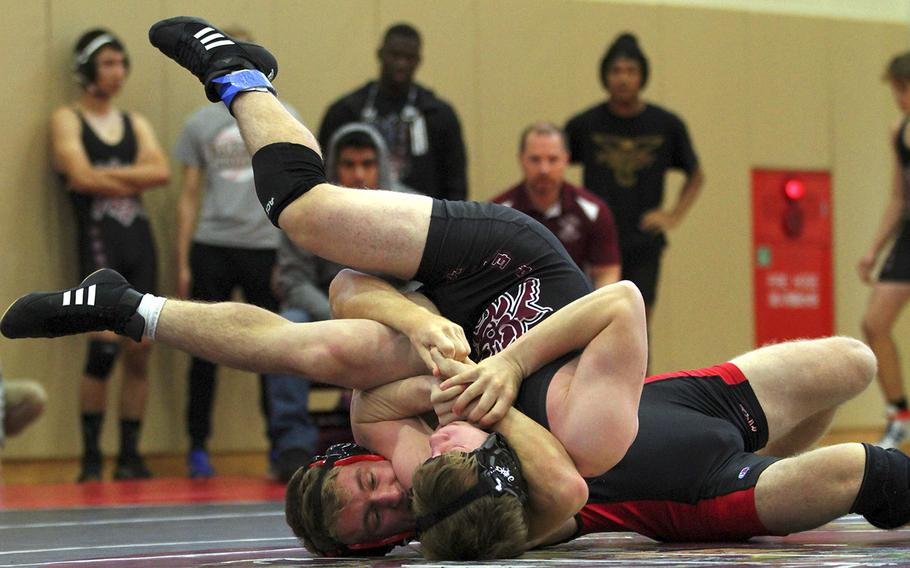 Nile C. Kinnick's Ethan Hamilton locks in a cradle on Matthew C. Perry's Parker Staley at 148 pounds during Saturday's DODEA-Japan dual meet tournament. Hamilton pinned Staley and the Red Devils won the dual meet 37-15.