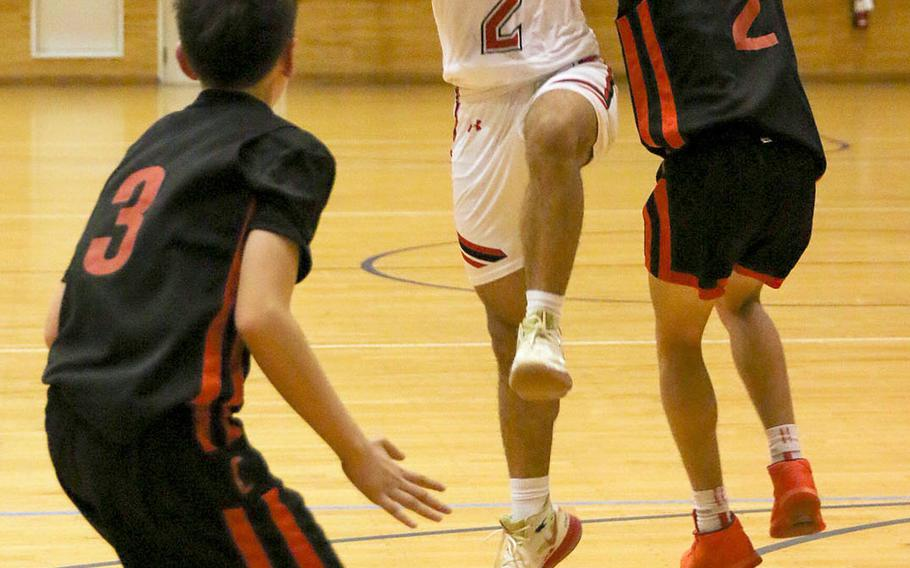 Nile C. Kinnick's James Mincey grabs the ball between E.J. King defenders Cameron Reinhart and James Meacham during Friday's DODEA-Japan boys basketball game. The Red Devils won 78-71.