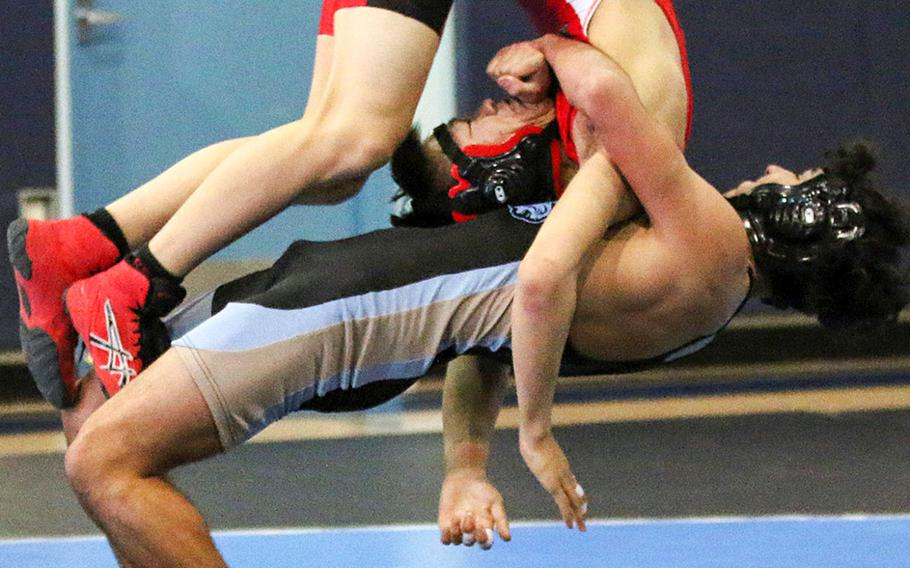 Osan's Zathain Soto does a back toss on Seoul Foreign's Max Nam at 129 pounds during Saturday's Korea wrestling tri-meet. Soto pinned Nam and the Cougars edged the Crusaders 29-26.