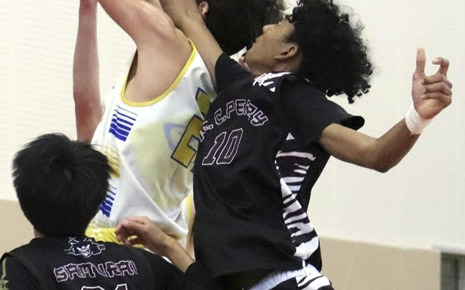 Yokota's Connor Rowan snags a rebound in front of Matthew C. Perry's Shion Fleming and Joseph Andres during Saturday's boys basketball game. The Samurai edged the Panthers 43-42.
