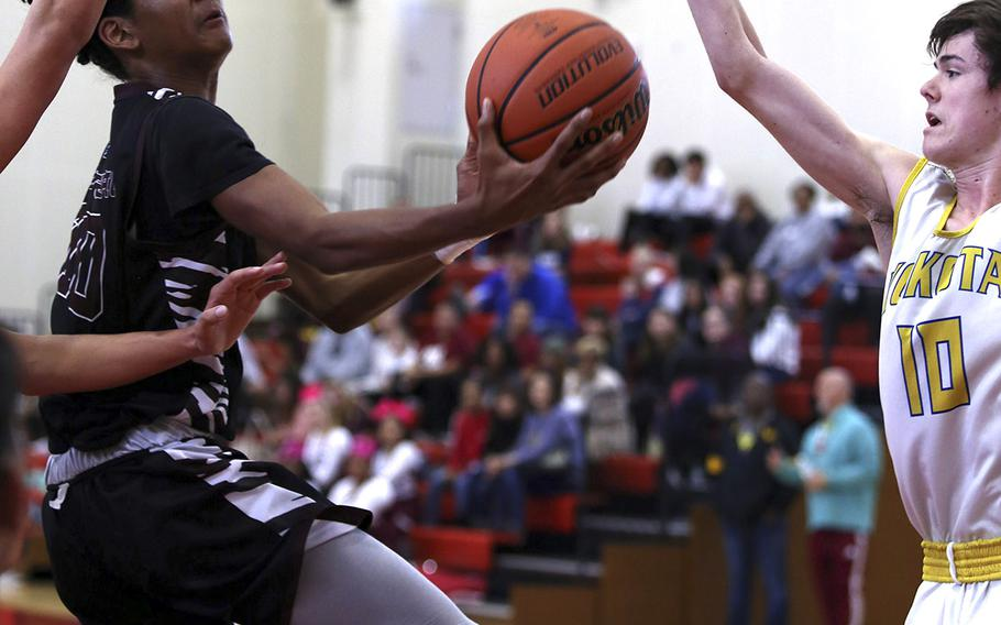 Matthew C. Perry's Shion Fleming drives for a shot against Yokota's Mickey Galvin to the basket during Saturday's boys basketball game. The Samurai edged the Panthers 43-42.