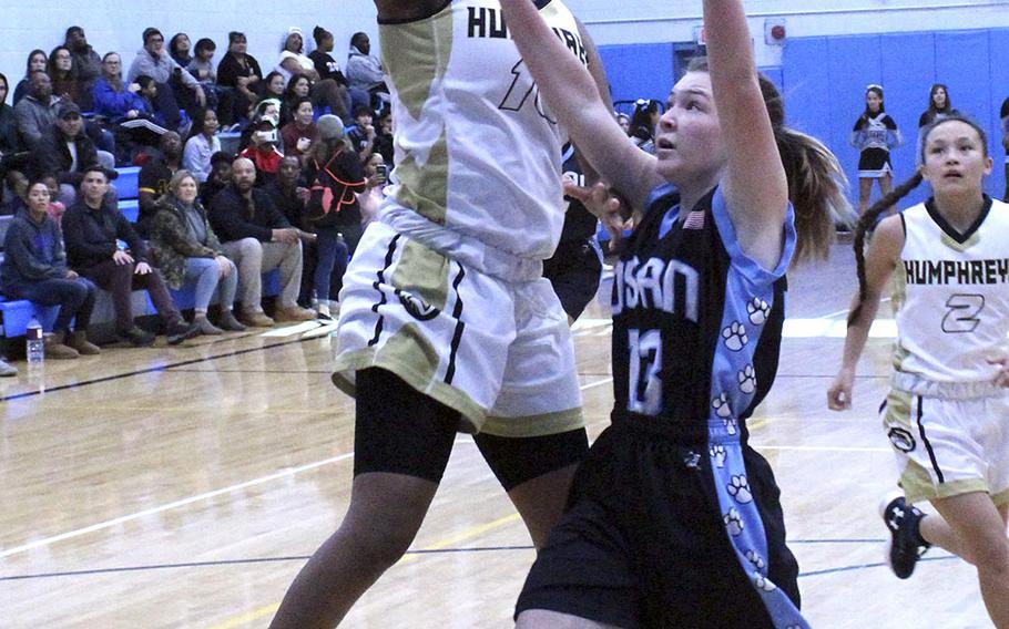 Humphreys' Jamaica Williams drives to the basket against Osan's Kennedy Liddell during Saturday's Korea Blue girls basketball game. The Blackhawks won 51-20.