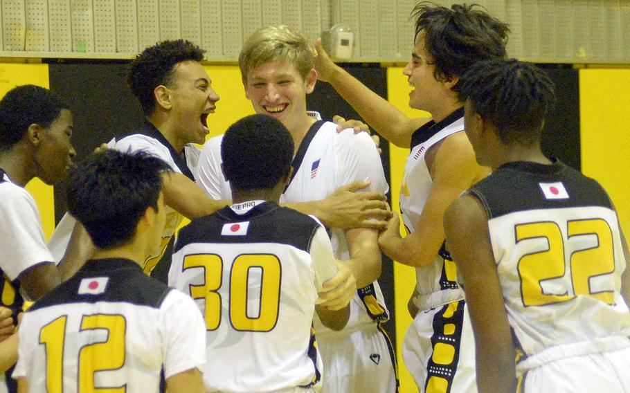 Kadena basketball players surround reserve Owen Caldwell, who scored the last basket of the game and his first of the season. as the buzzer sounded on the Panthers' 76-43 win Friday over Kubasaki.