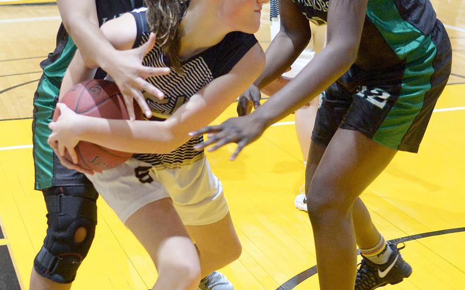 Taejon Christian's Katie Eggleston shields the ball from Daegu's Katrina Vasquez and Jya Van during Friday's Korea Blue girls basketball game. The Warriors won 54-22.