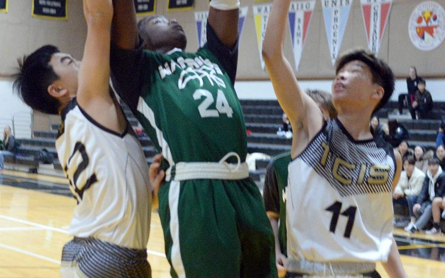 Daegu's Ziadee Barjolo grabs a rebound between Taejon Christian's Jaeson Pyeon and Josh Yun during Friday's Korea Blue boys basketball game. The Dragons won 47-26.