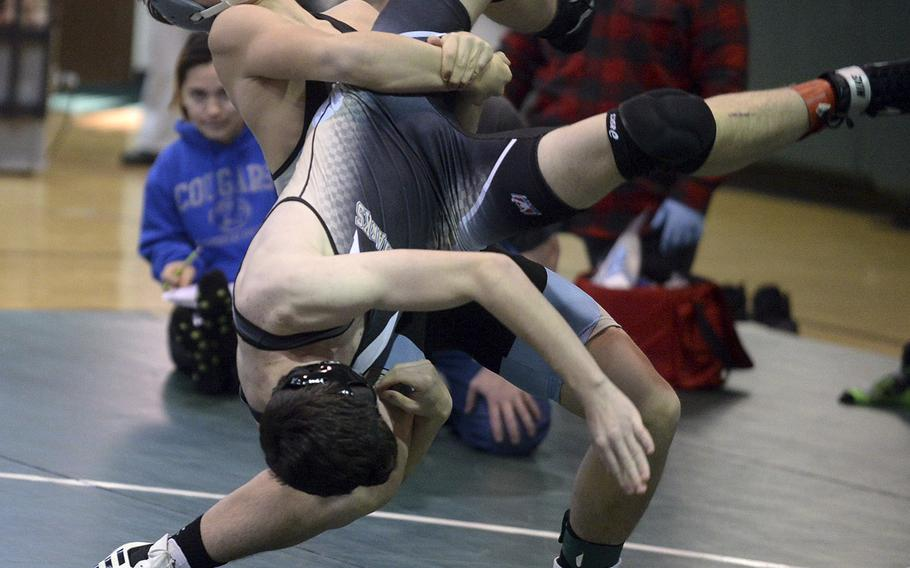 Osan's Toy Williams lifts Humphreys' Zack Downs at 141 pounds during Saturday's Daegu quad-meet. Williams won by technical fall 12-2.