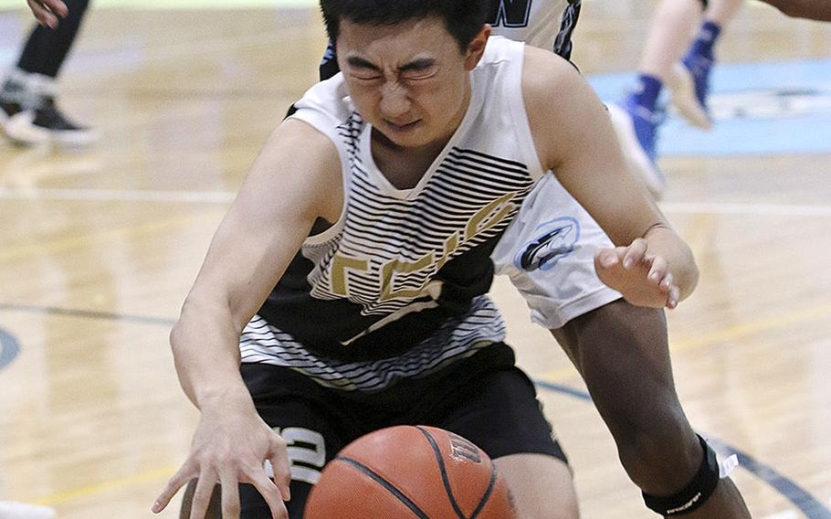 Taejon Christian International's Jaeson Pyeon is hemmed in by Osan's Bryson Goldsmith during Saturday's Korea Blue boys basketball game. The Cougars won their first game in six tries 67-44 over the Dragons.