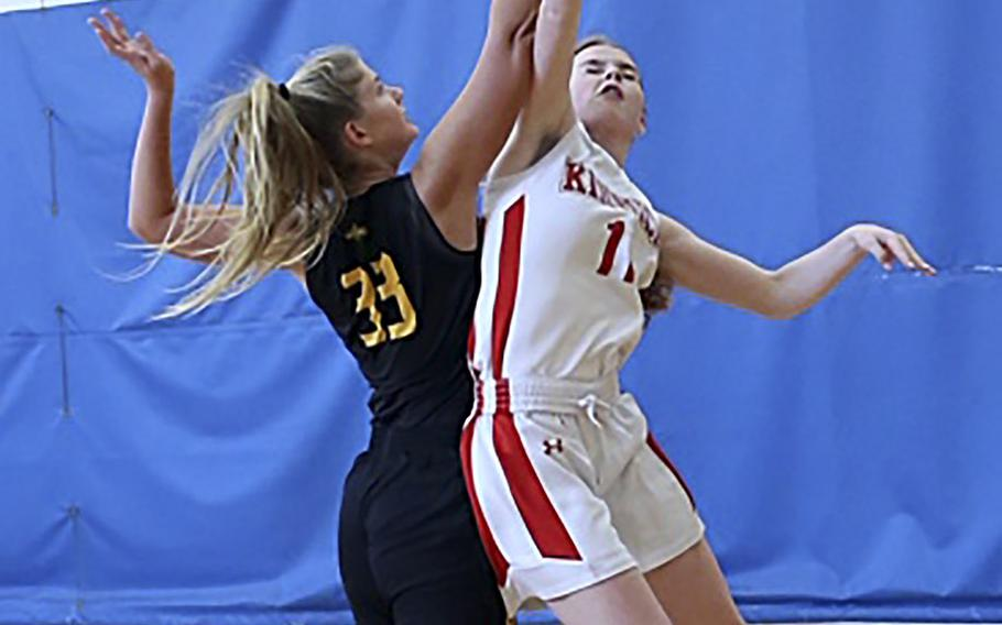 American School In Japan's Christiana Regent and Nile C. Kinnick's Cassi Boyer sky for the ball during Saturday's Kanto Plain girls basketball game. The Mustangs won 18-16.