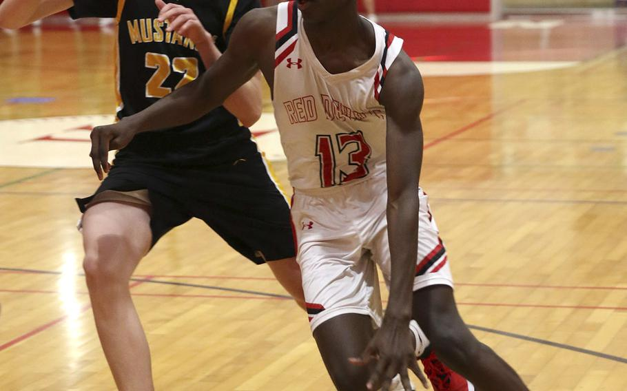 Nile C. Kinnick's Corey Hollingsworth drives past American School In Japan's Theo Welckle during Saturday's Kanto Plain boys basketball game. The Mustangs won 75-46.