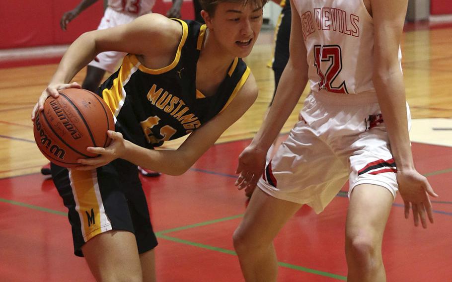American School In Japan's Max Murakumo-Mases looks for room against Nile C. Kinnick's Ethan Yuska during Saturday's Kanto Plain boys basketball game. The Mustangs won 75-46.