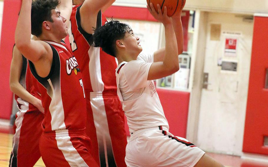 Nile C. Kinnick's Tristan Venturina drives for a shot against St. Maur defenders during Wednesday's Kanto Plain boys basketball game. The Red Devils won 86-27.