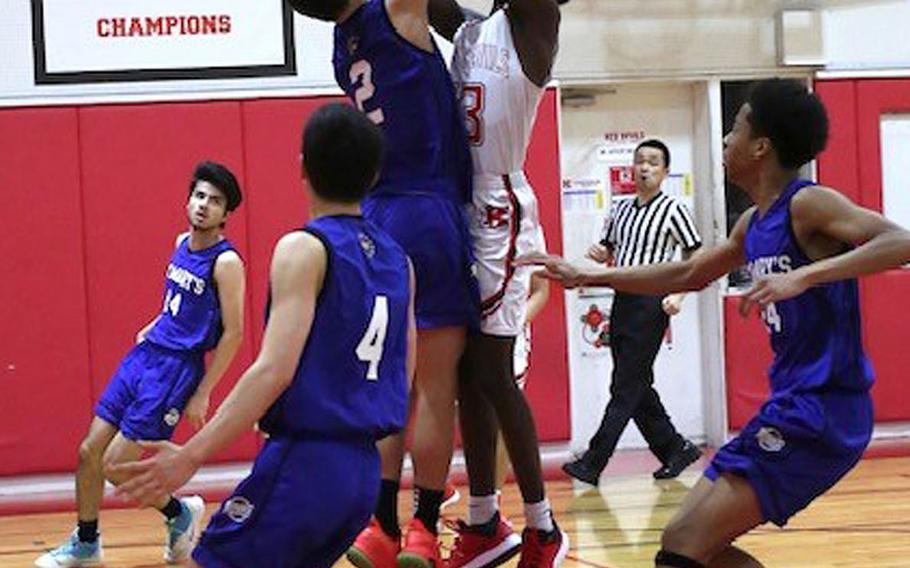 Nile C. Kinnick's Corey Hollingsworth shoots against St. Mary's Aidan O'Flaherty during Tuesday's Kanto Plain boys basketball game. The Titans won 74-54.