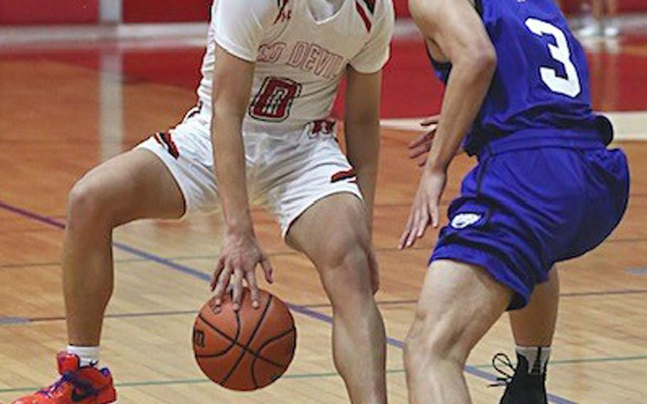 Nile C. Kinnick's Tristan Venturina dribbles against St. Mary's Jei Arai during Tuesday's Kanto Plain boys basketball game. The Titans won 74-54.