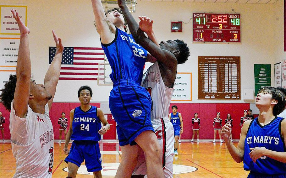 St. Mary's Lucas Wainwright leaps for a rebound against Nile C. Kinnick's Corey Hollingsworth during Tuesday's Kanto Plain boys basketball game. The Titans won 74-54.