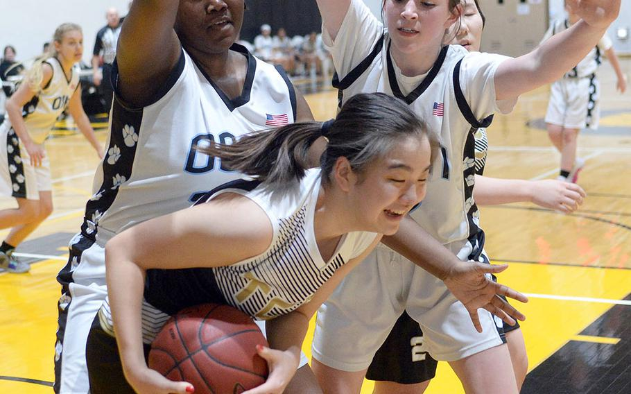 Taejon Christian's Amy Choi gets hemmed in by Osan's Cor'Rhyia Henry and Sadie Liddell during Tuesday's Korea Blue girls basketball game. The Dragons won 34-30.