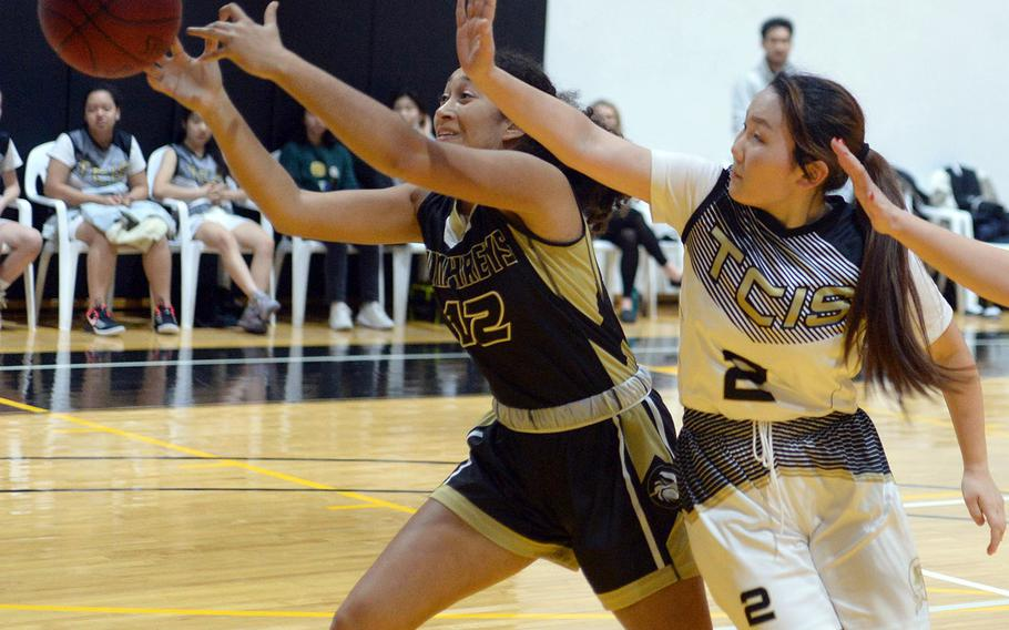 Humphreys' Melissa Pritchett can't quite find the handle on the ball in front of Taejon Christian's Minha Choi during Wednesday's Korea Blue girls basketball game. The Blackhawks won 44-17.